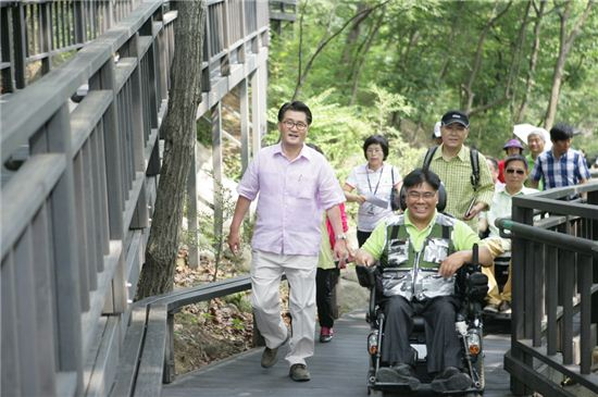 유종필 관악구청장이 민선6기 취임식 당일인 7월1일 장애인들과 함께 관악산 무장애숲길을 오르고 있다.