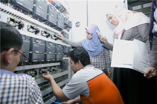 LG CNS가 국내 최초로 개발된 크로스벨트 소터 솔루션 '비바소터(VivaSorter)'를 적용, 말레이시아 최초 자동 물류처리센터를 구축한다. 말레이시아 포스라쥬 관계자들이 물류처리 제어패널을 테스트하고 있다.