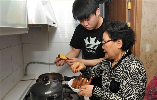 한 대학생이 할머니와 고구마를 먹으며 얘기를 나누고 있다.