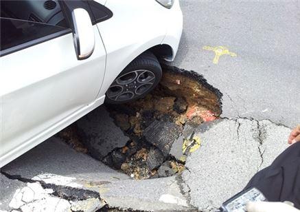 싱크홀이 발생한 도로를 차가 지나가고 있다.