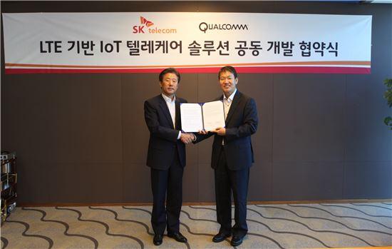 원성식 SK텔레콤 솔루션사업본부장(왼쪽)과 이태원 퀄컴코리아 부사장이 'IoT 기반 텔레케어 솔루션' 공동 개발을 위한 협약을 체결하고 악수를 나누고 있다.