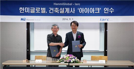 ▲유걸 아이아크 대표(왼쪽)와 김종훈 한미글로벌 회장(오른쪽)이 나란히 서서 악수를 하고 있다. 한미글로벌은 '비전 2020' 달성을 위해 건축 설계업체인 아이아크를 인수했다고 2일 밝혔다.