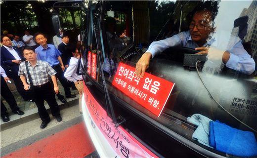 직행좌석버스 운전자가 입석금지 이후 좌석이 없다는 표시를 차량 앞면에 부착하고 있다.