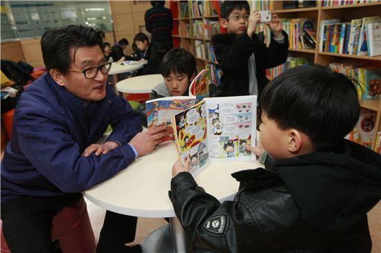 유종필 관악구청장이 일일동장으로 도서관에 들러 책 읽는 아이와 이야기를 나누고 있다.