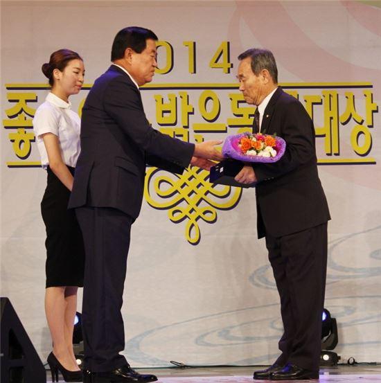 <한추향씨가 지난 12일 광주 김대중컨벤션센터에서 열린 '좋은 이웃 밝은 동네' 시상식에서 '좋은 이웃'으로 선정돼 이동진 진도군수로부터 으뜸상을 받고 있다.>