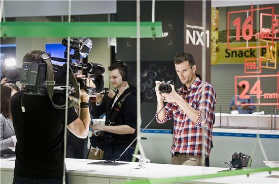 포토키나 삼성 NX 부스에서 글로벌 미디어 관계자들이 렌즈 교환형 미러리스 카메라 NX1을 체험하고 있다.