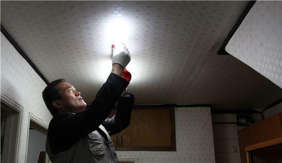 이상호 한국남부발전 사장이 부산지역 소외계층을 찾아 노후 전기설비를 교체하고 고효율의 LED등을 설치해주고 있다.