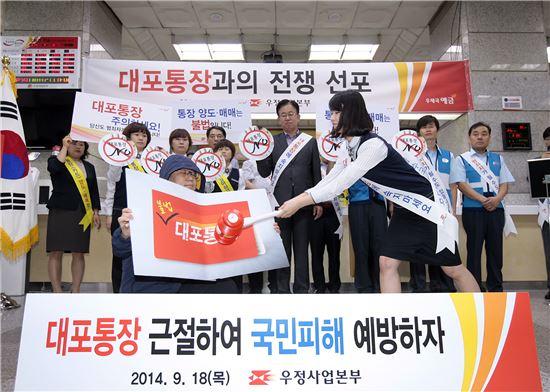 김준호 우정사업본부장(뒷줄 가운데)과 광화문우체국 직원들이 대포통장과의 전쟁을 선포하는 가운데 직원이 금융사기범의 대포통장을 부수고 있다.