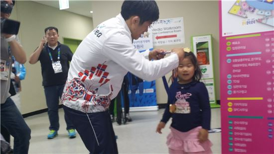 정지현이 큰딸 서현의 목에 금메달을 걸어주고 있다.[사진=이종길 기자]