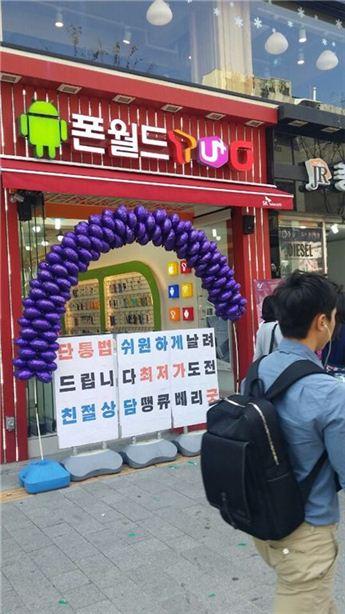 ▲단통법 시행 첫 주말인 3일, 대학가 휴대폰 판매점 앞을 사람들이 지나가고 있다.