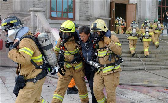 8일 경희대학교에서 열린 2014년도 재난대비 긴급구조 종합훈련에 참석한 주민들이 갑자기 발생한 불에 대피하고 있다.