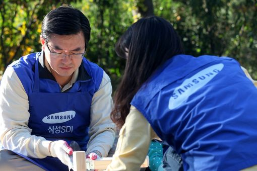 조남성 삼성SDI 소재부문 사장(왼쪽)이 16일 안양시 '평화의 집'에서 아동용 원목 책상을 만들고 있다.