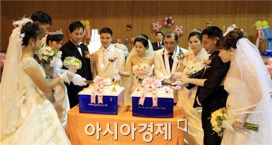 완도군민 축복속에 결혼식이 열린 다문화가정 5쌍이 케이크 자르고 있다.