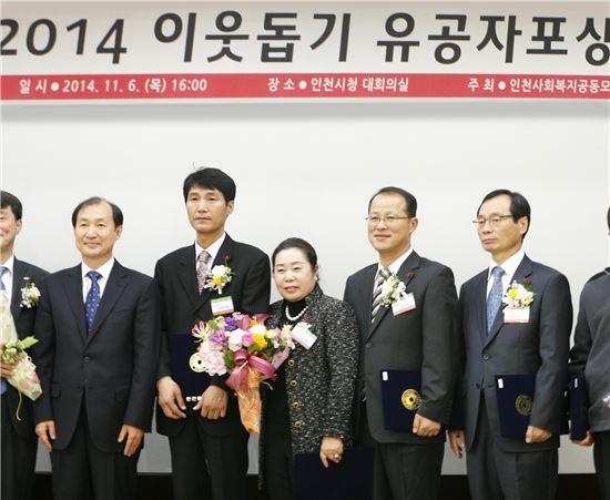 코베아 강혜근 회장(사진 가운데)이 '2014 이웃돕기 유공자' 선정 후 기념촬영을 하고 있다.