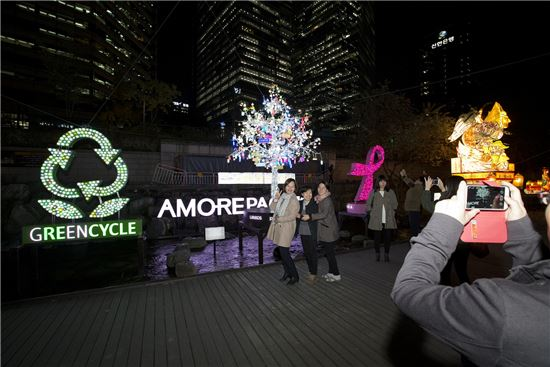 서울빛초롱축제에서 그린사이클 앰블럼,핑크리본캠페인 조형물, 공병트리 앞에서 사진을 찍고 있는 시민들