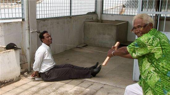 영화 '액트 오브 킬링' 안와르가 당시 사람들을 어떻게 죽였는지 재연하면서 웃고 있다.