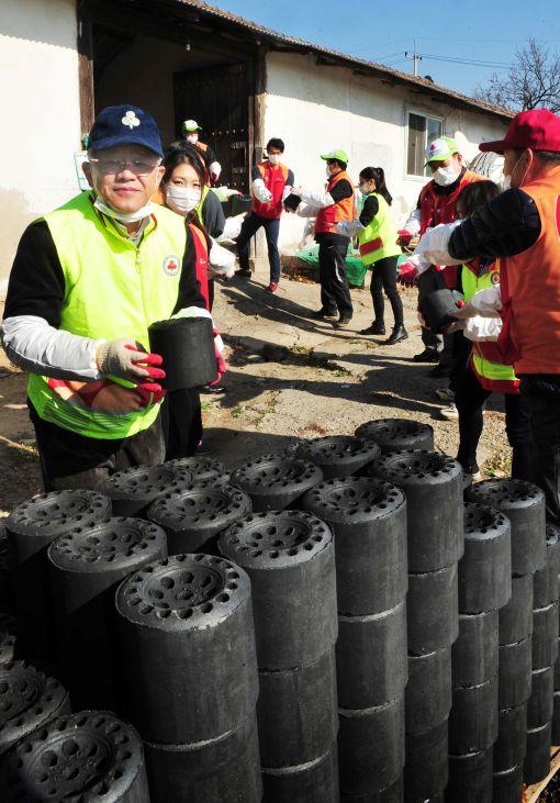 최신원SKC 회장(왼쪽 첫번째)이 10일 SKC, SK텔레시스, 경기모금회 직원들과 함께 경기도 여주 귀백리 마을에서 연탄 나르기 봉사활동을 하고 있다.
