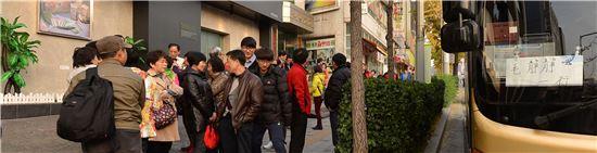 지난 19일 오후 버스에서 내린 관광객들이 서울 창천동에 위치한 '외국인전용 관광기념품 판매점'에 들어가기 위해 모여있다.