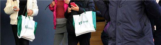 지난 19일 서울 창천동에 위치한 외국인전용 관광기념품 판매점에서 건강식품을 구매한 중국인 관광객들이 쇼핑백을 들고 나오고 있다.