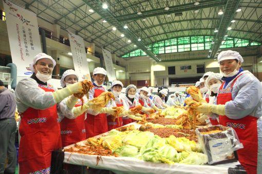 삼성토탈 손석원 사장(사진 맨 오른쪽)과 프란시스 랏츠 수석부사장(사진 맨 왼쪽)이 22일 '행복한 김장 나눔행사'에 참여해 직원들과 함께 맛있는 김치를 담그고 있다.