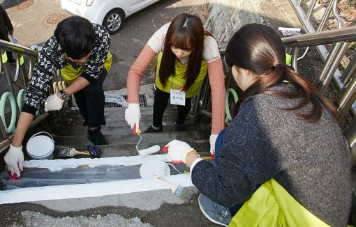 자원봉사자들이 고지대 계단에 페인트를 칠하고 있다.