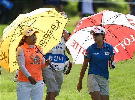 김효주(오른쪽)와 박인비가 각자의 후원사 로고가 크게 찍힌 우산을 쓰고 경기 도중 걸어가고 있다. 사진=KLPGA제공