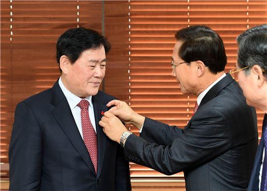 최 부총리가 사랑의열매 배지를 김주현 사회복지공동모금회 사무총장으로부터 받고 있다.