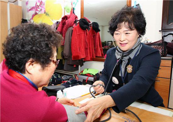 현보혜 간호사가 17일 사당4동 노인정을 찾아 방문 간호(혈압 측정)를 하고 있다.