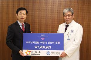 권윤순 아워홈 상무(왼쪽)가 한상원 세브란스 어린이병원 원장에게 희귀난치질환 아동을 위한 기부금을 전달하고 있다.