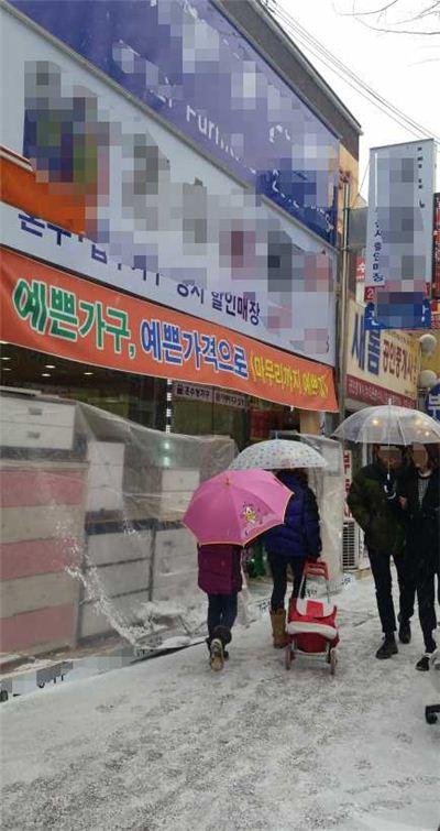 21일 광명 가구거리 앞의 한 매장을 행인들이 지나치고 있다.
