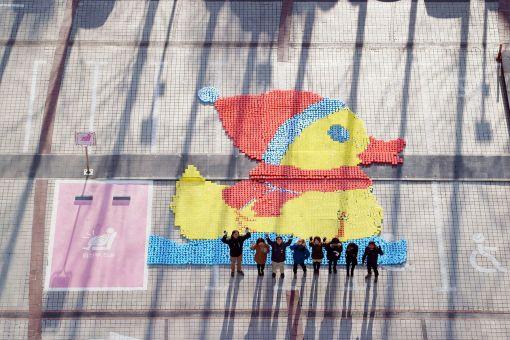 코오롱 사회봉사단이 완성된 산타덕 모자이크 앞에서 손을 흔들고 있다.