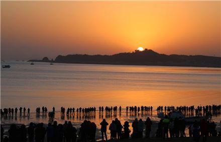 ▲올 1월1일 새벽 당진 왜목마을 해변에서 떠오르는 새해를 바라보고 있는 관광객들. (사진=당진시)