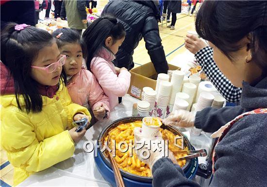 먹거리 장터에서 어린이들이  떡복이를 사고 있다.