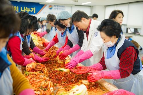 자생의료재단 신준식 이사장(오른쪽 가운데)이 25일 자생봉사단과 함께 김장김치 나누기 행사에 사용될 김장을 담고있다.