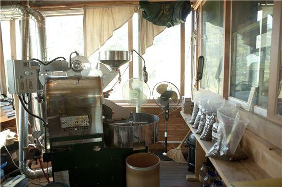 로스팅 기계와 원두, 커피와 관련된 책이 놓여 있는 공간.