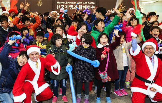 한국GM 한마음재단이 연말연시를 맞아 지난 15일 저녁 부평본사 홍보관에서 지역 장애인 복지시설 아동을 초청, '한국지엠과 함께 미리 즐기는 행복한 크리스마스 파티'를 갖고 의미 있는 시간을 보냈다. 사진은 이날 행사에 참석한 한국지엠 세르지오 호샤 사장 겸 CEO(앞줄 왼쪽), 대외정책부문 한주호 부사장(앞줄 오른쪽), 홍보부문 황지나 부사장(가운데)이 아이들과 함께 웃고있는 모습.