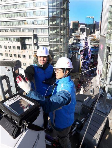 SK텔레콤 구성원들이 서울 명동거리 앞 기지국에서 네트워크 장비를 점검하고 있다.(사진=SKT)