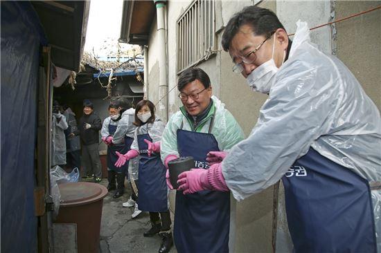 김원규 NH투자증권 사장(가운데)이 22일 영등포 쪽방촌을 찾아 임직원들과 함께 연탄을 나르고 있다.