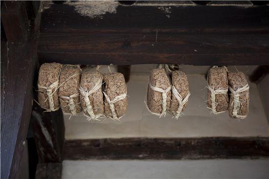 주인 부부가 농사 지은 콩으로 만든 둥그런 메주가 익어간다.
