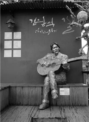 골목길 초입에 있는 기타치는 김광석 조형물
