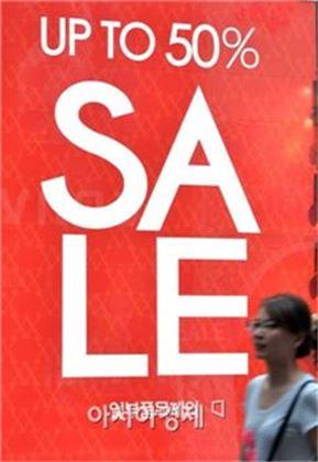 ▲한 시민이 50% 할인 광고가 붙은 매장 앞을 지나가고 있다. 사진=아시아경제DB