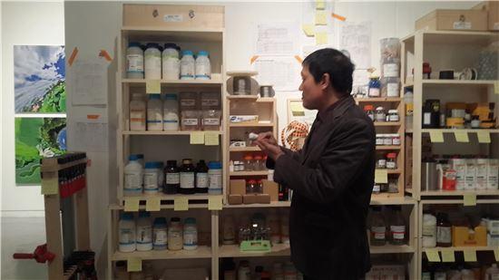 실제 작업에 사용하는 물감, 화학재료들을 설명하고 있는 주도양 작가.