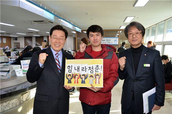 이재명 성남시장이 청년배당 수령을 위해 동주민센터를 방문한 젊은이와 화이팅을 외치며 기념사진을 찍고 있다.