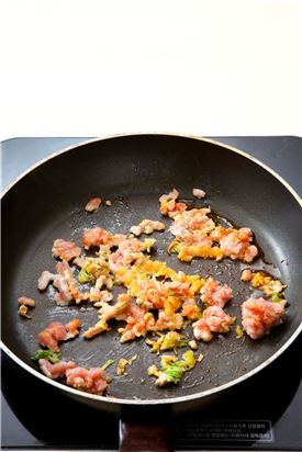 2. 프라이팬에 고추기름 1을 두르고 돼지고기, 다진 파, 다진 마늘, 다진 생강을 넣어 볶는다.