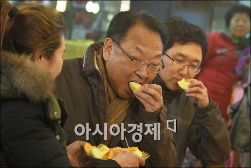 [포토]사과 시식하는 유일호 부총리