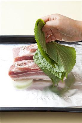 4. 돼지고기에 깻잎을 2~3장씩 겹쳐 덮어서 오븐 팬에 양파를 깔고 올려 220도에서 30분 정도 익힌다.
