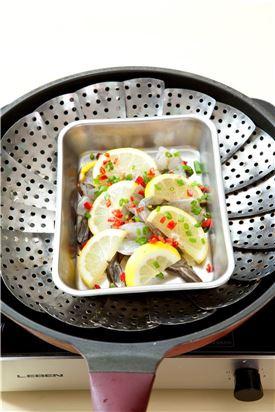 4. 그릇에 새우를 담고 레몬, 홍고추, 다진 마늘, 다진 생강, 실파를 뿌린 다음 김이 오른 찜통에 넣어 8-10분 정도 찐다.
