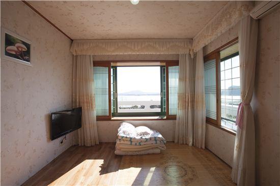 민박집의 안채 2층 방에서는 창문 너머로 제주의 바다가 아련하게 보인다.