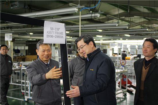 주영섭 중소기업청장(앞줄 오른쪽)이 9일 (주)파버나인 생산현장을 방문해 이 회사 이제훈 대표(왼쪽)로부터 제품설명을 듣고 있다.