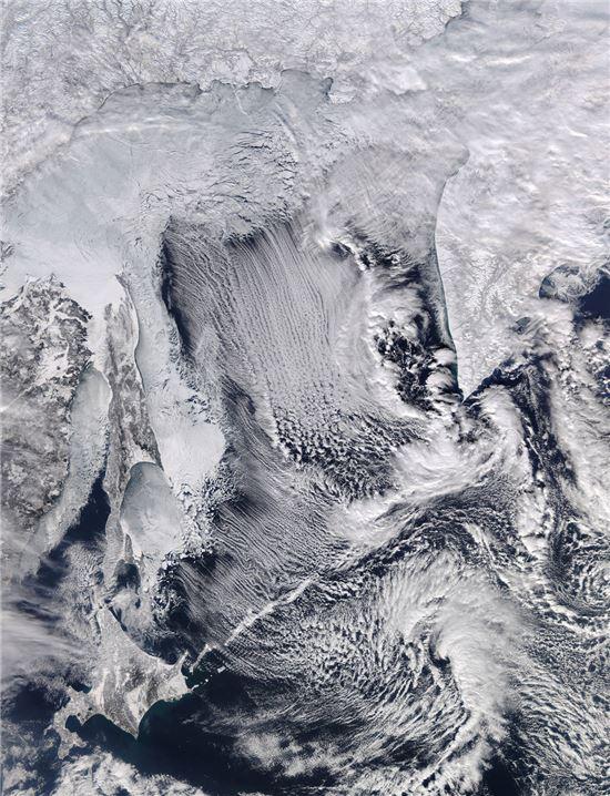 ▲오호츠크 해에 해빙과 구름길이 펼쳐져 있다.[사진제공=NASA]